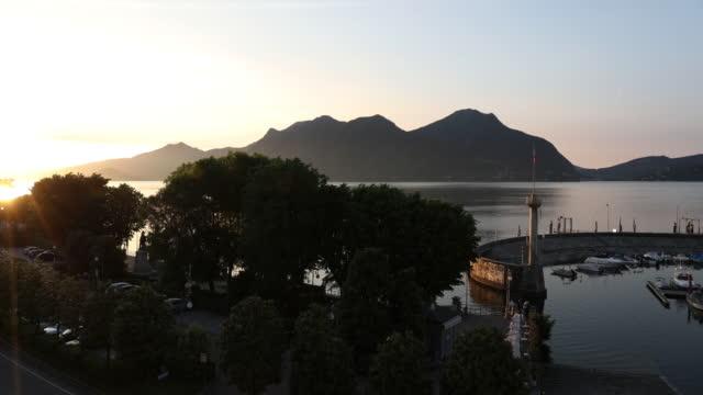 vídeos de stock e filmes b-roll de time lapse view of sun rising over lake and pier - lago maggiore