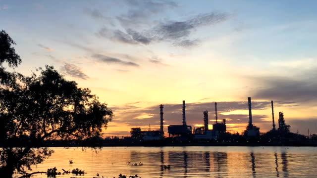 stockvideo's en b-roll-footage met time-lapse: weergave raffinaderij met rivier reflectie - olieraffinaderij