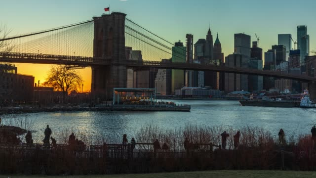 tids fördröjning-visa till manhattan skyline från dumbo brooklyn bridge park i solnedgången. - strandnära bildbanksvideor och videomaterial från bakom kulisserna