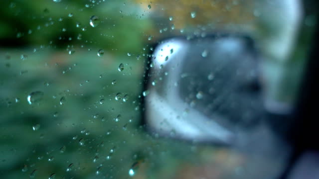 Time lapse water drops on window with glass side mirror car background during rain. Time lapse water drops on window with glass side mirror car background during rain. uk border stock videos & royalty-free footage