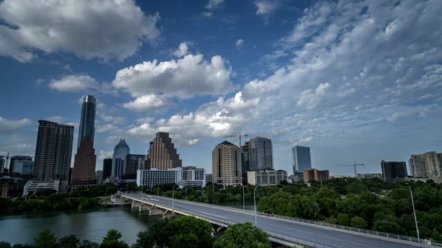 Time lapse White Clouds over Downtown Austin Buildings with Congress Bridge in the Foreground
