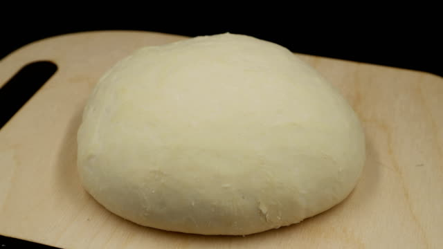 time lapse. yeast dough increases in size. the dough on the cutting board rises on black background. - impasto video stock e b–roll