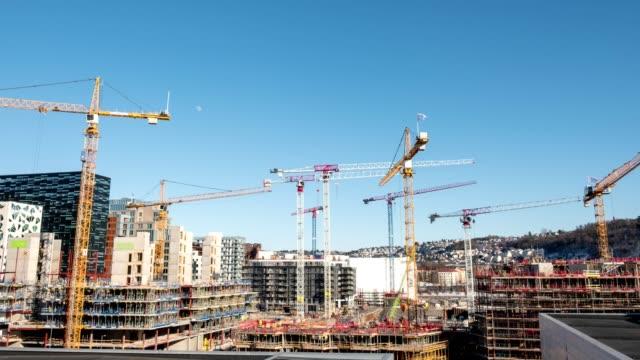 vídeos de stock, filmes e b-roll de zoom de lapso de tempo em edifício de construção com guindastes e derrick e céu azul na cidade - nova casa
