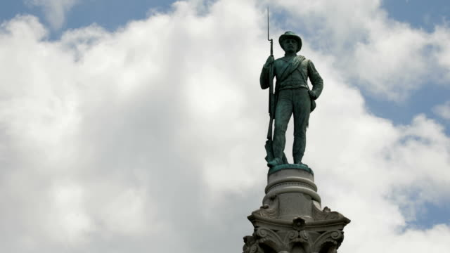 vídeos de stock e filmes b-roll de time lapse zoom out of clouds behind statue of soldier - monumento
