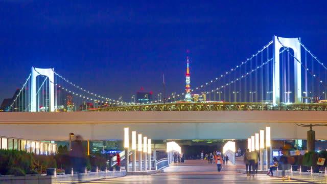 4k tidsfördröjning zooma ut: rainbow bridge viewpoint med bilfria publiken at night - odaiba kaihin koen bildbanksvideor och videomaterial från bakom kulisserna