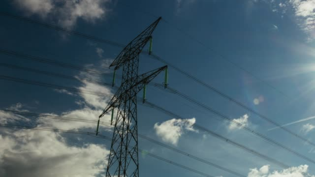 Time lapse zooming out of high voltage power lines Transmission towers in Normandy, France. Cloud scape on a bright sunny day with sunbeams in the sky. Electric power generation industry concept. Close up high voltage sign stock videos & royalty-free footage