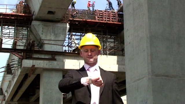 Time management A construction manager looks at his watch. craftsman architecture stock videos & royalty-free footage