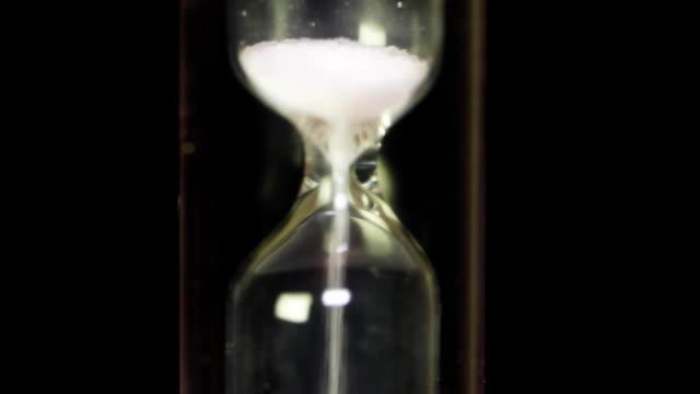 tiden går - glas timglas med vit sand på blackbackground. klassisk stil vintage gamla timglas sandglass klockan. makro - ancient white background bildbanksvideor och videomaterial från bakom kulisserna