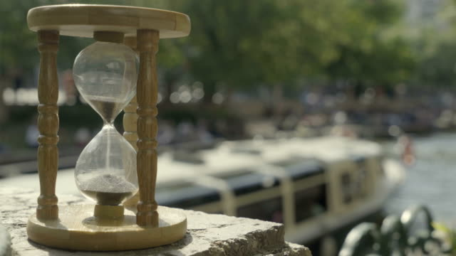 Time running out with sand in hourglass, defocused passenger ship in river