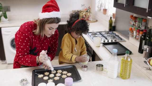 Time to make these cookies look more festive 4k video footage of a mother and her little son baking together during Christmas at home decoration stock videos & royalty-free footage