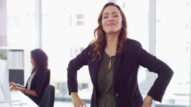 Time to take charge of your success 4k video footage of a confident young businesswoman working in a modern office with her colleague in the background arms akimbo stock videos & royalty-free footage