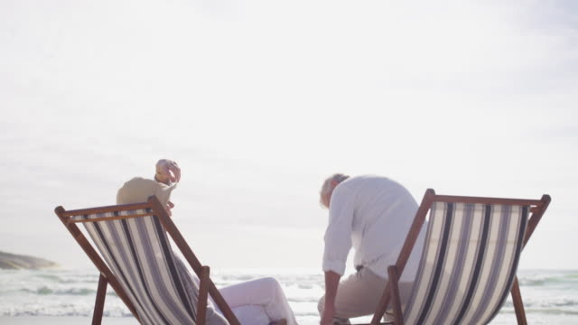 Time to unwind, together 4k video footage of a happy mature couple relaxing on chairs at the beach lounge chair stock videos & royalty-free footage