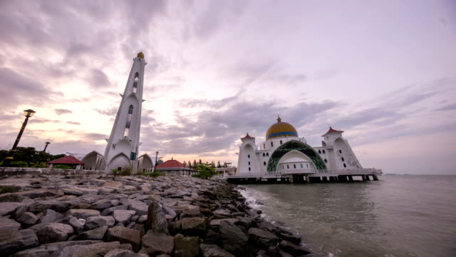 timelapse 4k footage of a beautiful sunrise at Melaka Strait Mosque with moving and changing color clouds. video