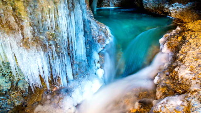 4K Timelapse. A freezing waterfall and a lake in a cave in winter video
