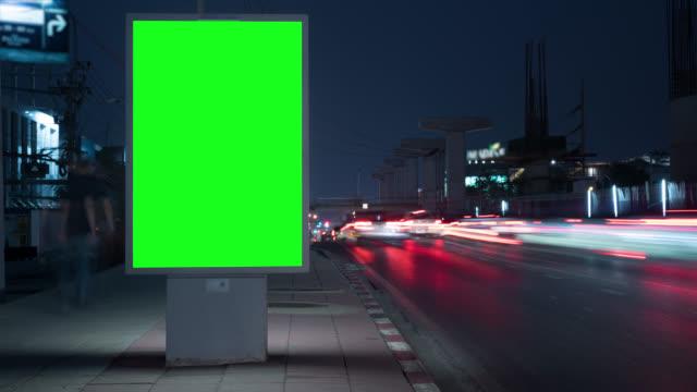 vídeos de stock, filmes e b-roll de timelapse anuncia outdoor na rua à noite com tráfego - poster