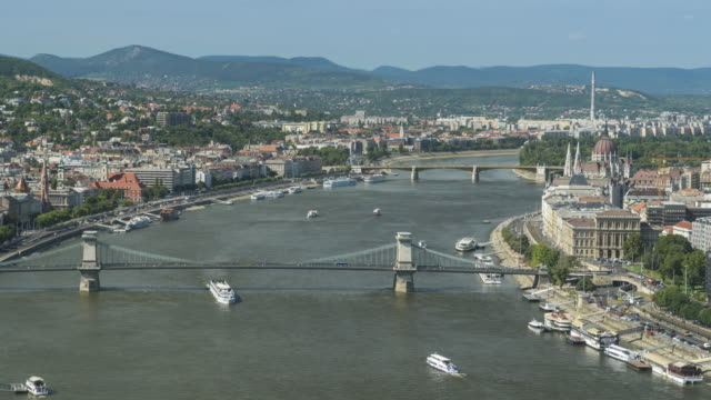 Timelapse Aerial side view of suspension history bridge and city in Budapest, Hungary, Szechenyi Chain Bridge at the weekend. many transportations, nautical vessel, tour boat along the Danube river. Concept of travel destination with urban skyline.