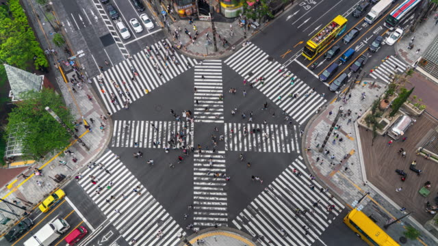4K Timelapse Aerial View of Crowd People pedestrians and Cars Crossing Intersection Road in Ginza, Tokyo, Japan 4K Timelapse Aerial View of Crowd People pedestrians and Cars Crossing Intersection Road in Ginza, Tokyo, Japan traffic time lapse stock videos & royalty-free footage