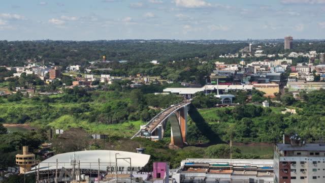 замедленная съемка аэрофотоснимок дружбы моста (ponte da amizade), смежной фос сделать игуасу, бразилия, сьюдад-дель-эсте, парагвай - парагвай стоковые видео и кадры b-roll