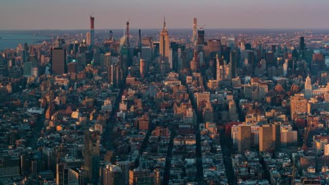 vídeos de stock, filmes e b-roll de time-lapse: vista aérea do horizonte da cidade de nova york no crepúsculo do pôr do sol da cidade - new york city