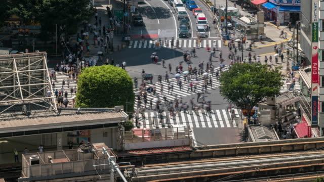 time-lapse: flygfoto av fotgängare trångt korsning och tågstationen i shibuya tokyo japan - billboard train station bildbanksvideor och videomaterial från bakom kulisserna