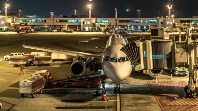 stockvideo's en b-roll-footage met time-lapse: aankomst van het vliegtuig naar terminal jetway dock night - schiphol