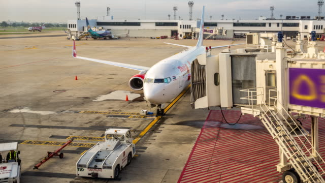 stockvideo's en b-roll-footage met 4 k time-lapse: aankomst van het vliegtuig naar terminal jetway dock - schiphol