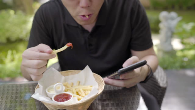 Timelapse - Asian man eating fast food, unhealthy snack meal. french fries chips dipping in ketchup while playing Mobile Phone