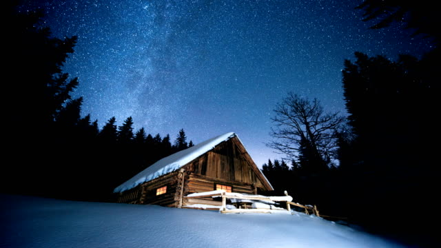 time-lapse. beautiful wooden house in the winter forest under the stars - capanna video stock e b–roll