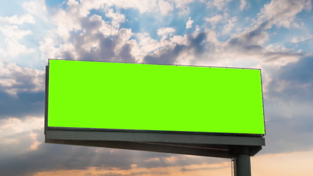 Timelapse - blank green billboard and sun beams shining through clouds at sunset Timelapse: blank wide green billboard or large display with sun beams shining through clouds at sunset. Consumerism, time lapse, advertising, green screen, mock up, copy space, chroma key concept billboard stock videos & royalty-free footage