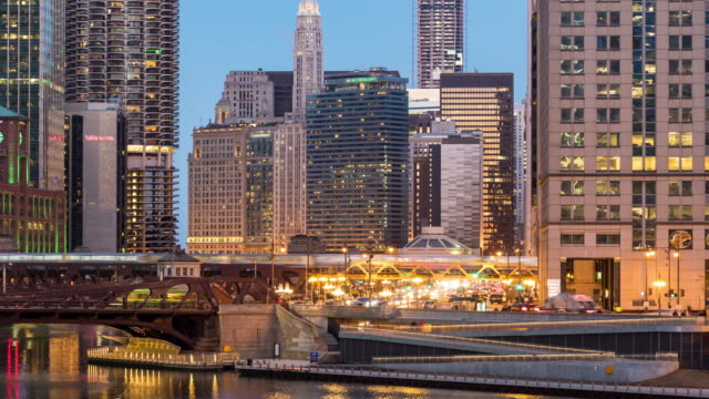 Time-lapse: Chicago Skyline Buildings at downtown with Chicago River near Wolf point, IL USA at sunset twilight