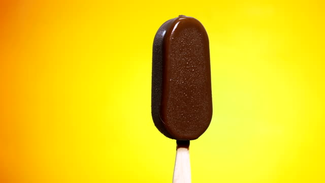 time-lapse: chocolate coated ice cream melting on yellow background - stopić się filmów i materiałów b-roll