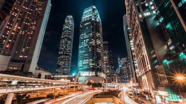 stockvideo's en b-roll-footage met 4k uhd time-lapse stadsgezicht bij nacht van hong kong stad zakendistrict met stoplicht routes en kantoorgebouwen, uitzoomen effect. - financieel district