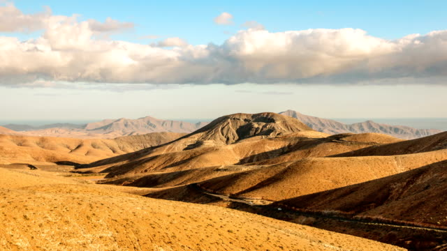 timelapse clouds flying over dry mountains and smooth hills, fuerteventura, spain - deser filmów i materiałów b-roll