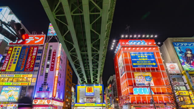 4K Time-lapse : Crowds across road below colorful signs in Akihabara. (panning down view) video