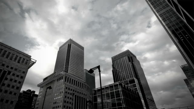 time-lapse. dark clouds over canary wharf - black and white architecture stock videos & royalty-free footage