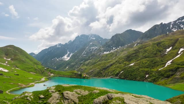 Timelapse emerald green alpine lake moving clouds, Italy