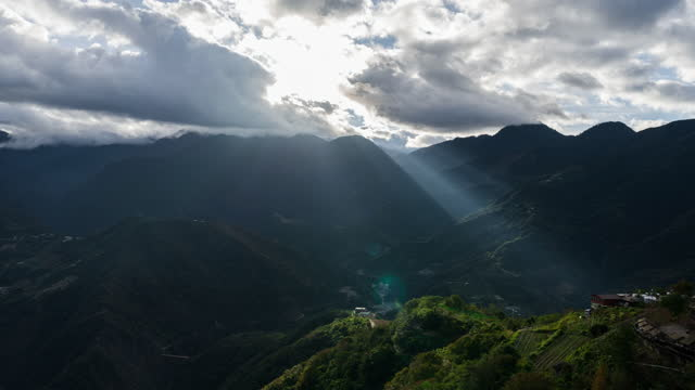 4K Time-lapse fog above mountain and sunlight through clouds at sunrise