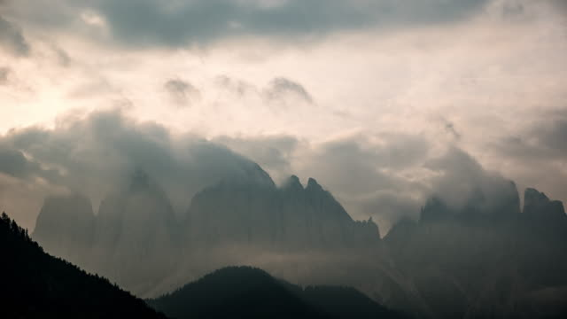 Timelapse Fog rolls across flowing over mountains video