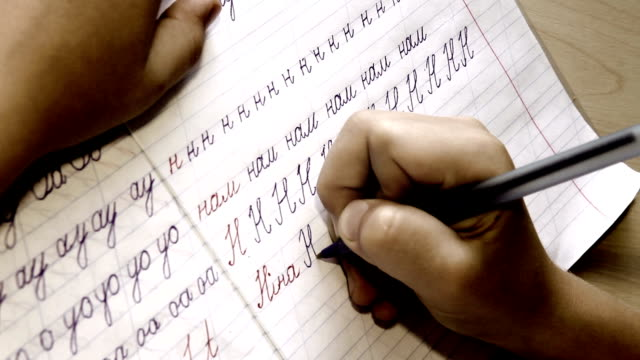 Timelapse footage:: little boy writes letters in diagonal lined notebook video