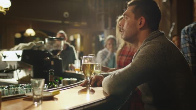 vídeos de stock e filmes b-roll de timelapse filmes de um homem sentado sozinho com cerveja em um bar enquanto as pessoas estão ter bom tempo. - bêbedo