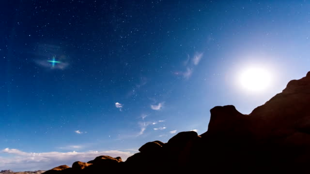 Timelapse footage of night sky with full moon rising, or moonrise, in Goblin Valley State Park in Utah showing clouds, stars, and canyons silhouttes in wilderness nature video
