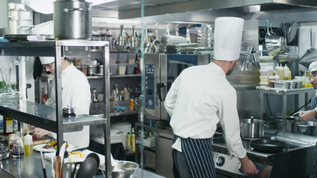 Timelapse footage of three professional chefs in a commercial kitchen in a restaurant or hotel preparing food. video