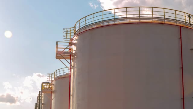 timelapse gas reservoirs with service grounds against sky