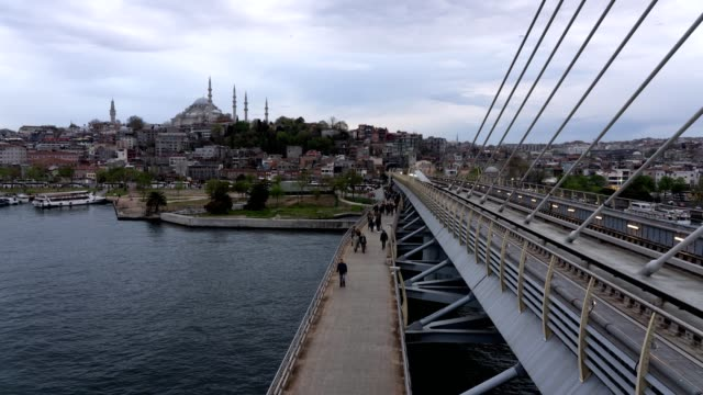 Timelapse Golden Horn Metro Bridge and People walking on the bridge and Mosque is at the background.