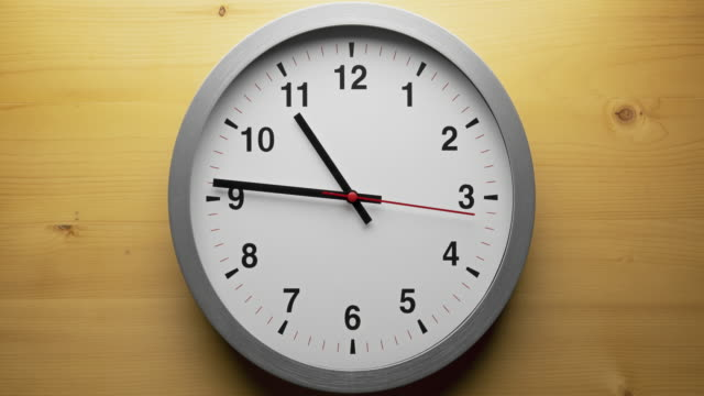 Time-lapse gray clock with black arrows shows motion the time speed up from 10.00 to 12.00, How time flies concept.