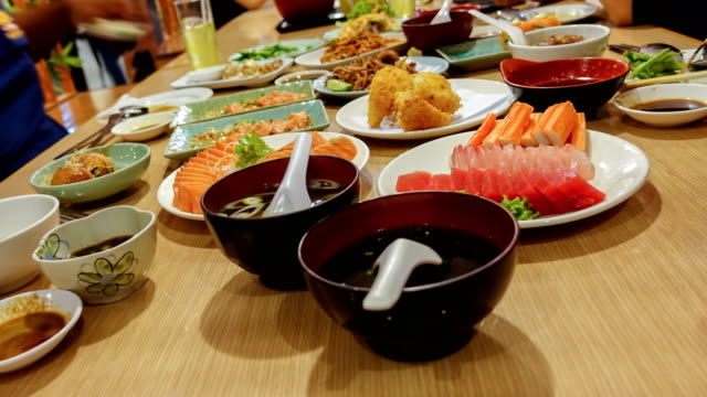 Timelapse Group of Friend eating with chopsticks takes sushi from a plate in a japanese restaurant. Timelapse Group of Friend eating with chopsticks takes sushi from a plate in a japanese restaurant. sashimi stock videos & royalty-free footage
