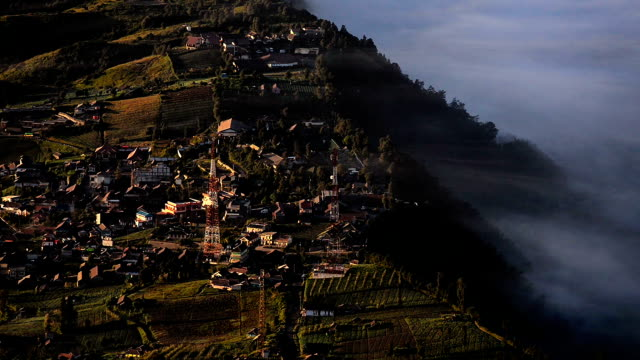 Time-lapse High angle shot Fog over top Cemoro Lawang village near at mount bromo video