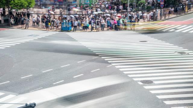 vídeos y material grabado en eventos de stock de 4k timelapse vista de gran angular gran foto de hombre y mujer turista peatonal caminando por el cruce de la calle con coches de conducción en la carretera en el fin de semana de verano en shibuya, tokio, japón - señalización vial