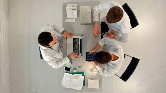 timelapse hospital, medicinsk utbildning, hälsovård, människor och medicin koncept - grupp glada läkare med tablet pc-datorer möte på läkarmottagning. ovanifrån - hospital studio bildbanksvideor och videomaterial från bakom kulisserna