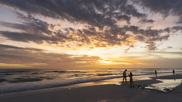 Timelapse in 4k of sunset at Siesta Key beach in Sarasota Florida with people walking along beach and children playing and building a sand castle along the Gulf of Mexico